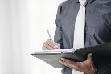 Close-up image of businessman signing contracts in folder